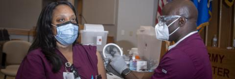 Nurse receives vaccine from her coworker, both are wearing masks