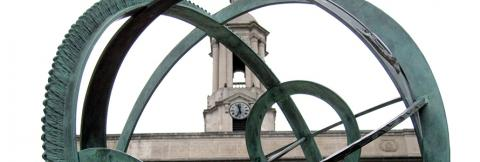 The Old Main Bell Tower sits behind the Old Main Armillary Sphere on the Pennsylvania State University campus.