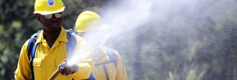 A first responder in a hard hat holds a hose spraying water; a second first responder in a hard hat stands behind.